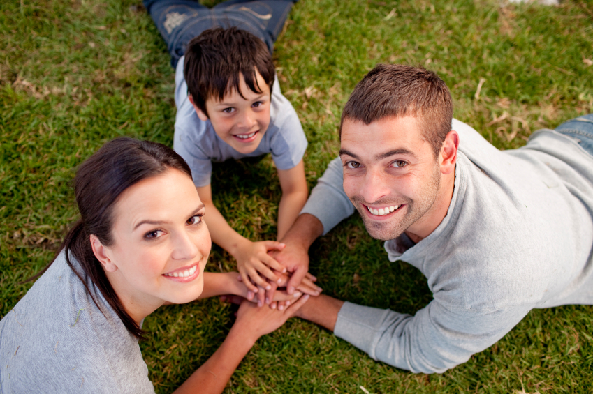 Parents and kid lying on garden with hands together