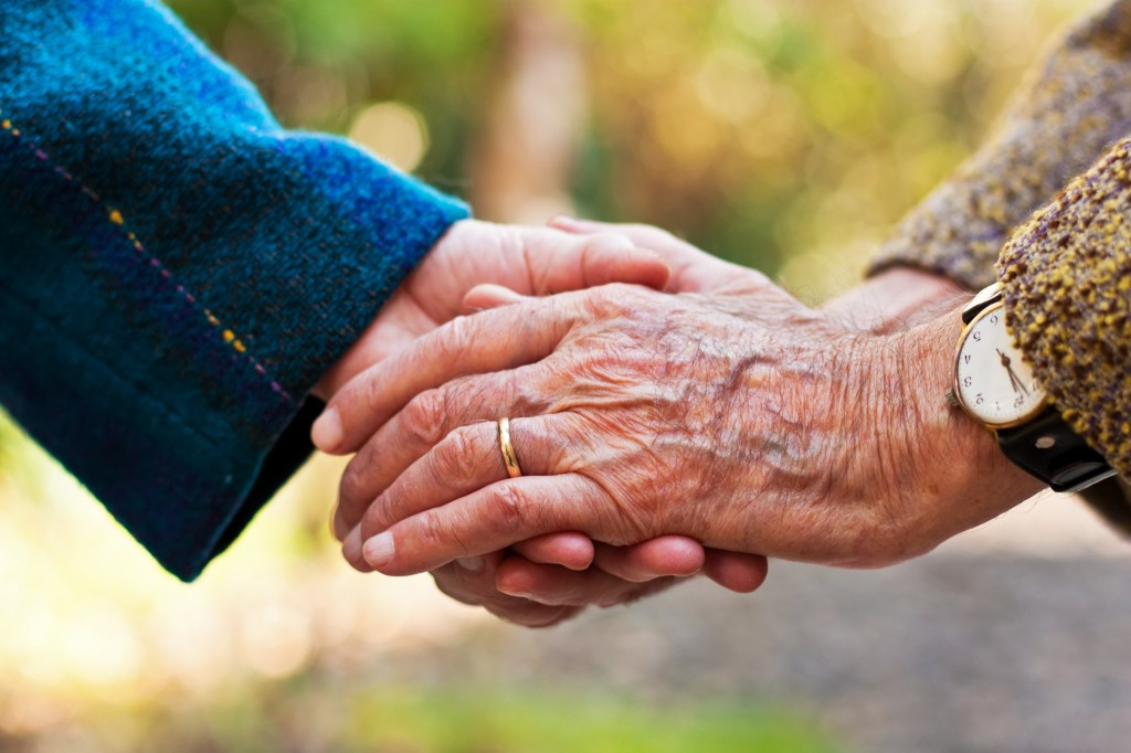 18078797 - elderly couple holding hands outdoors