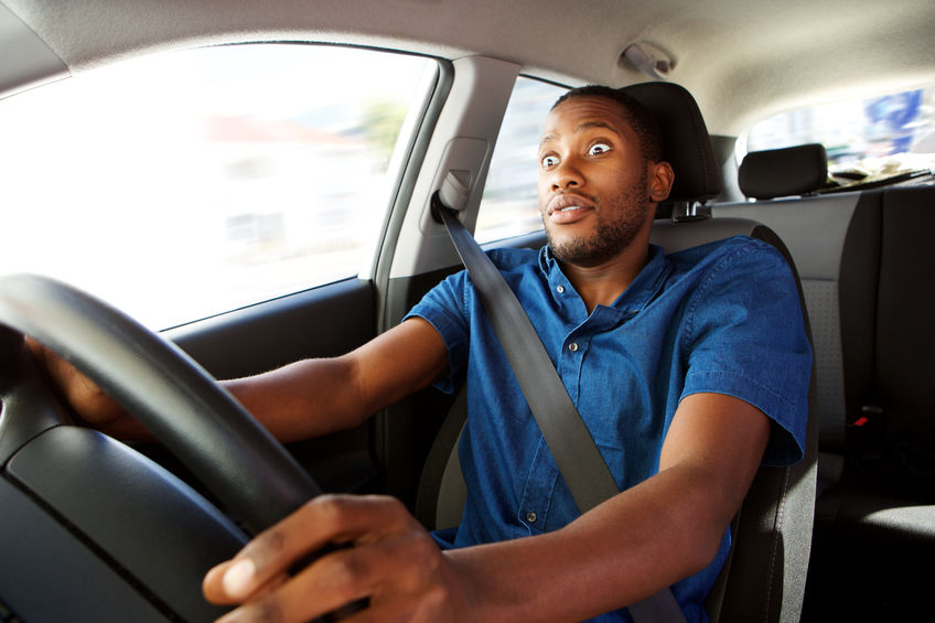 Young man driving a car with surprised expression