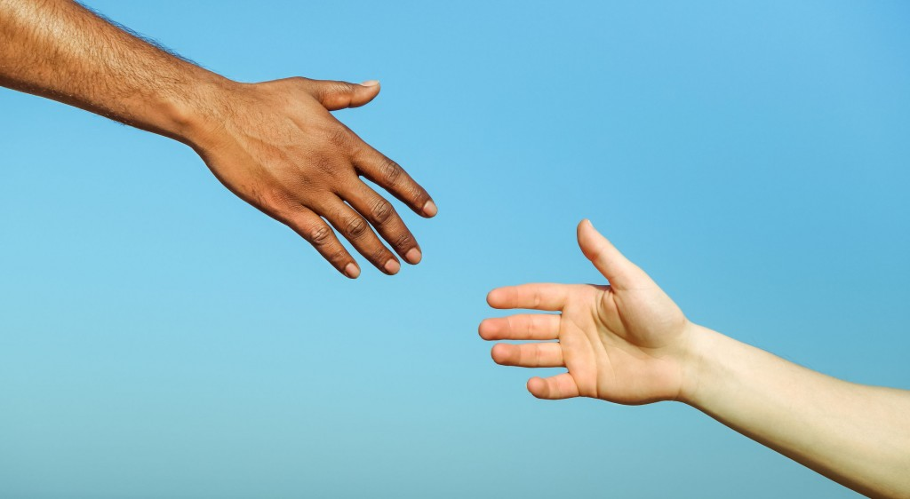 Black hand man helping white person - Different skin color hands