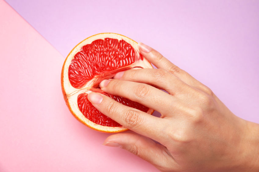 Young woman touching half of grapefruit on color background, above view. Sex concept