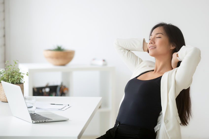 Relaxed happy asian woman enjoying break at workplace breathing