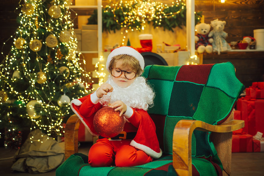 Sad Santa. Flu in Christmas time. Cute boy with a Christmas tree toy is sitting in a chair with sad emotions. Lonely child on holidays without parents. Children frustration.
