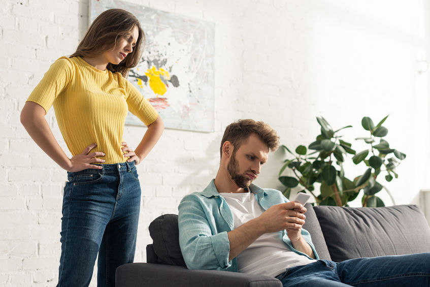 Angry woman with hands on hips standing near smartphone depended man on couch