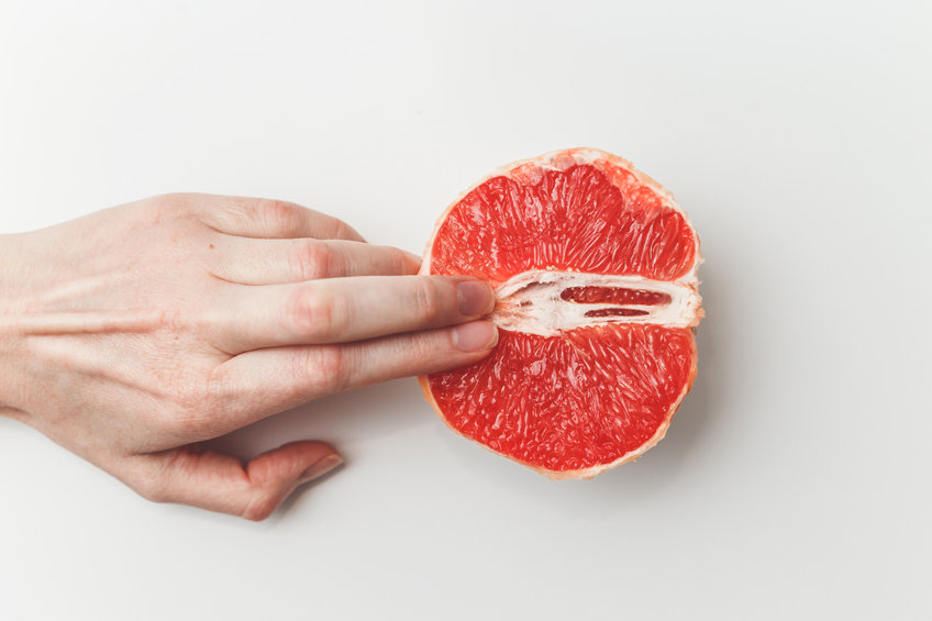 Sexual and female genital concept. Grapefruit and women's fingers like vagina and clitoris symbol